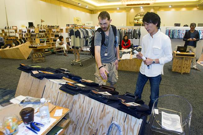 Sean Barry, left, of New York looks over Momotaro (Peach Boy) Jeans with Tabuchi Tatsushi during the Modern Assembly fashion trade show at the Sands Expo & Convention Center Wednesday, Aug. 20, 2014. Barry said Japanese jeans age in unique ways reflecting their wearer's usage. The jeans take their name from a popular Japanese folktale because  the folktale is believed to have originated in Okayama, Japan where the company is based. The show is a collection of six shows: The Accessories Show, Agenda, Capsule, Liberty, Mrket, and Stitch.