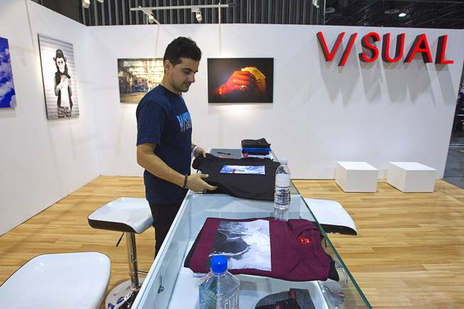 Navid Saedi, a marketing associate with Visual, folds T-shirts during the Modern Assembly fashion trade show at the Sands Expo & Convention Center Wednesday, Aug. 20, 2014. The company was started by photographer Van Styles so the booth was created with an Art Gallery feel, Saedi said. The show is a collection of six shows: The Accessories Show, Agenda, Capsule, Liberty, Mrket, and Stitch.
