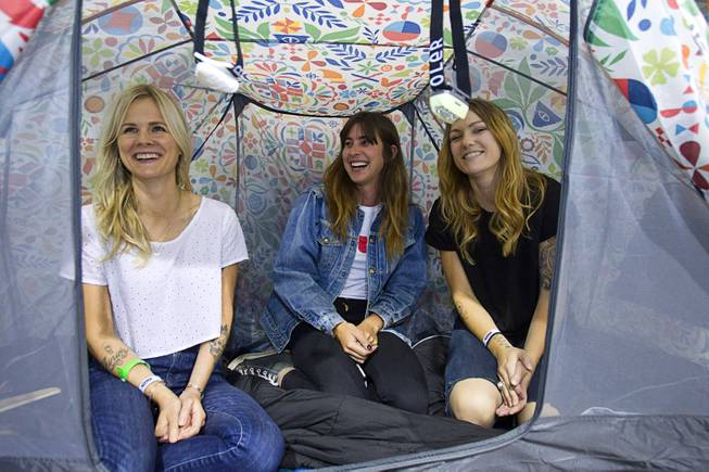 "Kara Murff, left, Julia Heit, center, and Tori George pose in a ""Rainbro"" pattern tent during the Modern Assembly fashion trade show at the Sands Expo & Convention Center Wednesday, Aug. 20, 2014. The Rainbro line of tents and Napsack sleeping bag are available online and will be in stores this fall, George said. The show is a collection of six shows: The Accessories Show, Agenda, Capsule, Liberty, Mrket, and Stitch."