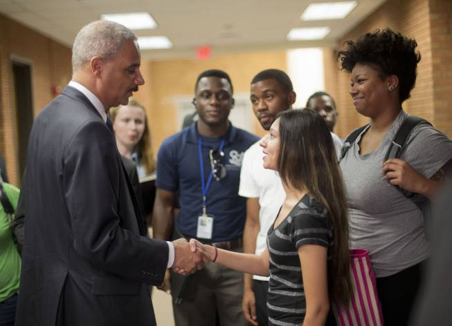 Attorney General Eric Holder shakes hands with Bri Ehsan, 25, right, following his meeting with students at St. Louis Community College Florissant Valley in Ferguson, Mo., Wednesday, Aug. 20, 2014.