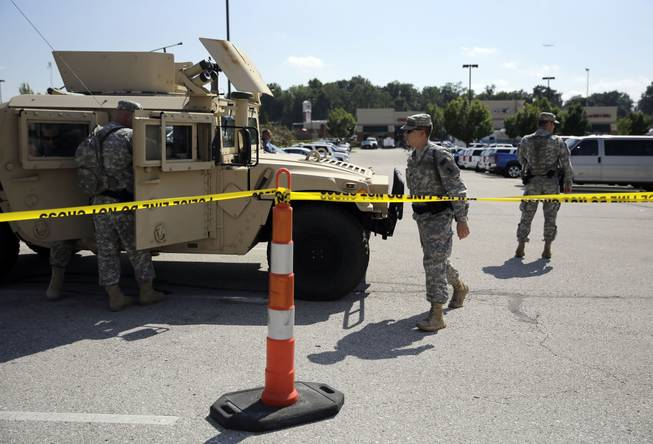 Members of the Missouri National Guard secure the perimeter of a police command post Tuesday, Aug. 19, 2014, in Ferguson, Mo.
