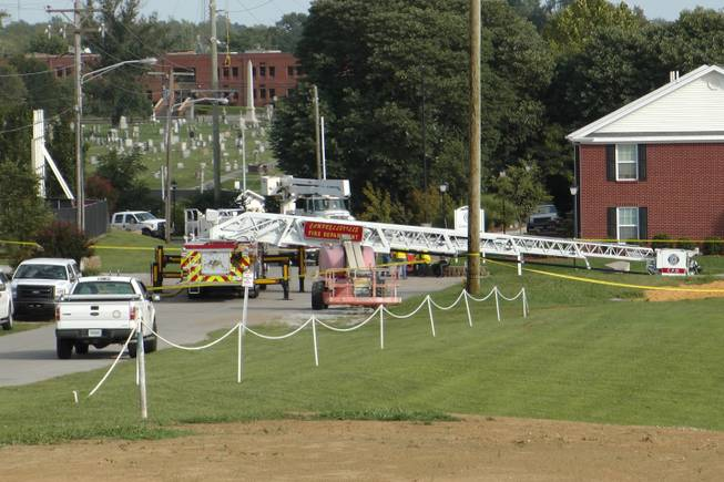 A Campbellsville Fire Department truck with the ladder extended remained at the scene where two firefighters were injured during an ice bucket challenge during a fundraiser for ALS on Thursday, Aug. 21, 2014, in Campbellsville, Ky. Officials say the ladder got too close to a power line and electricity traveled to the ladder, shocking the firefighters.
