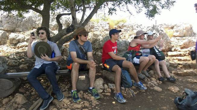 In this 2014 photo provided by Michigan State University, students in the school's Summer Study Abroad Program take a break while hiking in Israel. Some U.S. colleges have now pulled students from their overseas study programs in Israel as the Gaza war rages. Colleges site security as the top concern.