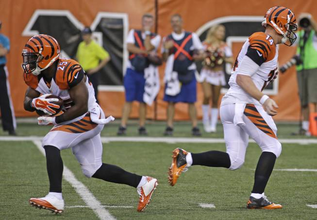 Cincinnati Bengals quarterback Andy Dalton (14) hands off to running back Giovani Bernard (25) in the first half of an NFL preseason football game against the New York Jets, Saturday, Aug. 16, 2014, in Cincinnati.