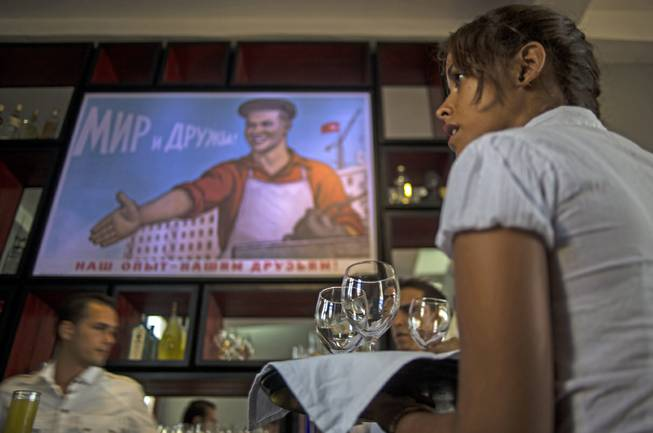 In this Wednesday, Aug. 20, 2014, photo, a waitress works during the pre-launch rehearsal at the new restaurant Nazdarovie, where the reproduction of a Soviet propaganda poster hangs over the bar area in Havana, Cuba. The new retro-Soviet restaurant serves minty mojitos, but they come mixed with vodka instead of the traditional white rum.