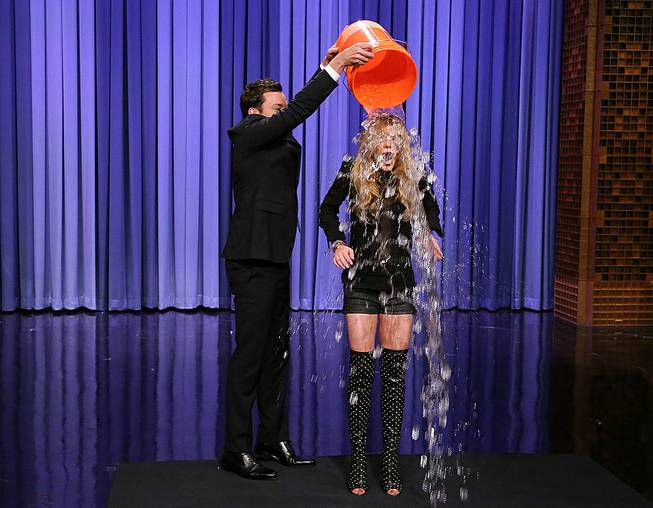 "This Aug. 20, 2014 photo released by NBC shows host Jimmy Fallon, left, dumping a bucket of ice water over the head of actress Lindsay Lohan as she participates in the ALS Ice Bucket Challenge on ""The Tonight Show Starring Jimmy Fallon,"" in New York."