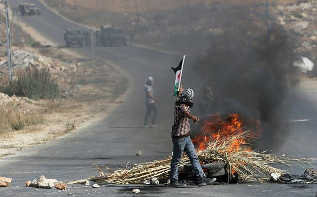 Palestinian protesters face Israeli soldiers during clashes, following a protest against the Israeli military action in Gaza, in the West Bank city of Nablus on Friday, Aug. 22, 2014.