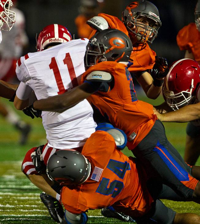 Bishop Gorman defenders team up to sack Brophy Prep QB Cade Knox on their way to a 44-0 win on Friday, August 22, 2014.