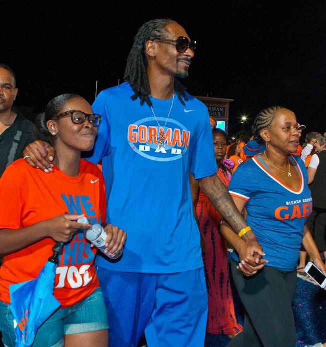 Snoop Dogg leaves the field with his family members after Bishop Gorman handily beat Brophy Prep 44-0 on Friday, August 22, 2014.
