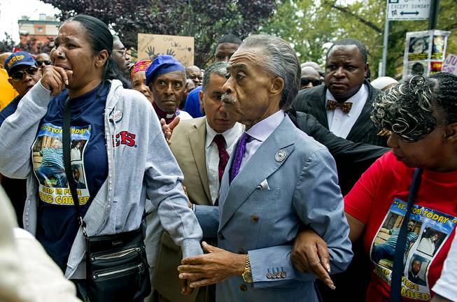Esaw Garner, left, arrives at the spot where her husband Eric Garner died with The Rev. Al Sharpton, center, and Eric Garner's mother Gwen Carr, right, at the start of a march and rally in the Staten Island borough of New York, Saturday, Aug. 23, 2014. The city medical examiner ruled that Eric Garner, 43, died as a result of a police chokehold during an attempted arrest.
