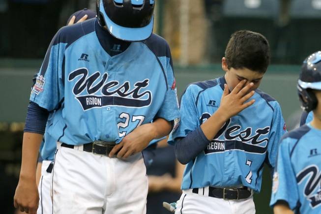 Las Vegas' Brennan Holligan (27), and Josiah Cromwick (7) walk off the field after a 7-6 loss to Chicago in the United States Championship game at the Little League World Series tournament in South Williamsport, Pa., Saturday, Aug. 23, 2014. (AP Photo/Gene J. Puskar