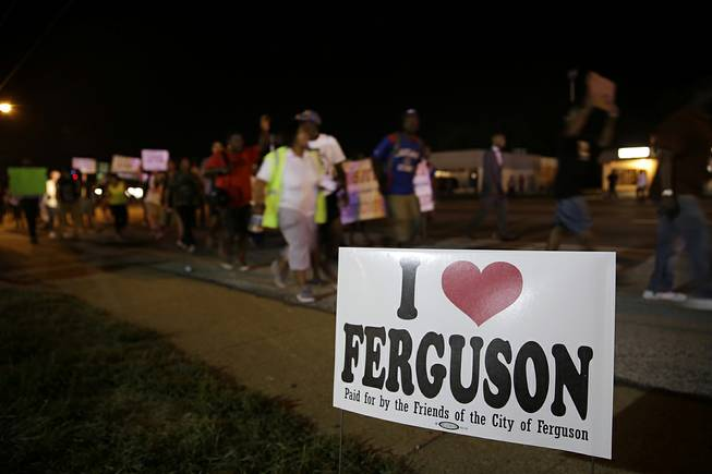 Protesters march Thursday, Aug. 21, 2014, in Ferguson, Mo. Protesters again gathered Thursday evening, walking in laps near the spot where Michael Brown was shot. Some were in organized groups, such as clergy members. More signs reflected calls by protesters to remove the prosecutor from the case.