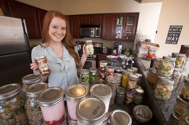 "Chelsea Meggerson poses with Mason jars of food in her kitchen Sunday, Aug. 24, 2014. At left is ""pizza in a jar"" and  at right is a jar of shrimp tacos. Meggerson, a UNLV student, provides a service where she provides families with fresh meals in Mason jars. She shares her recipes on her website theinspiregreen.com."