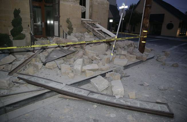 Rubble covers the sidewalk in front of the Vintners Collective multi-winery tasting room following an earthquake Sunday, Aug. 24, 2014, in Napa, Calif. A large earthquake rolled through California's northern Bay Area early Sunday, damaging some buildings, igniting fires, knocking out power to tens of thousands and sending residents running out of their homes in the darkness.