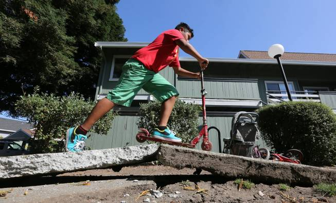 A youngster rides his scooter over a sidewalk buckled by an earthquake Sunday, Aug. 24, 2014, in Napa, Calif. A large earthquake caused significant damage and left at least three critically injured in California's northern Bay Area early Sunday, igniting fires, sending at least 87 people to a hospital, knocking out power to tens of thousands and sending residents running out of their homes in the darkness.