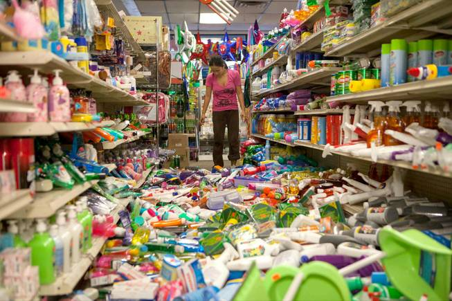Nina Quidit cleans up the Dollar Plus and Party Supplies Store in American Canyon Calif. after an earthquake on Sunday Aug. 24, 2014. Quidit and her husband were woken up in the early morning hours by the store's alarm company and immediately drove in to begin clean up. The 6.0-magnitude quake caused six significant fires, including at four mobile homes, Napa Division Fire Chief Darren Drake said.