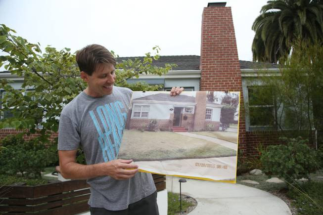 Rick Blankenship holds a photo of his previous grass lawn at his home in Long Beach, Calif. As Californians face a historic drought, more people are tearing out thirsty grass lawns to cut down on water use.