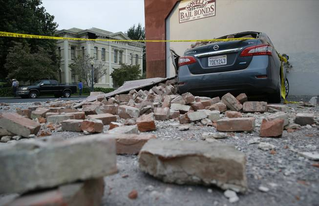 Bricks and fallen rubble cover a car with the old courthouse in the background after an earthquake Sunday, Aug. 24, 2014, in Napa, Calif. A large earthquake rolled through California's northern Bay Area early Sunday, damaging buildings, igniting fires, knocking out power to tens of thousands and sending residents running from their homes in the darkness.