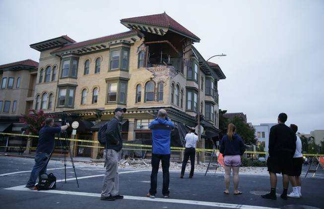 People look at a damaged building with a top corner exposed following an earthquake Sunday, Aug. 24, 2014, in Napa, Calif. A large earthquake rolled through California's northern Bay Area early Sunday, damaging some buildings, igniting fires, knocking out power to tens of thousands and sending residents running out of their homes in the darkness.