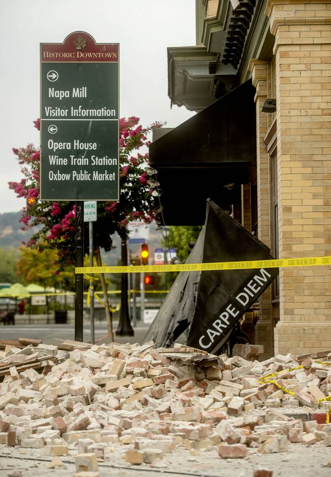 An awning for Carpe Diem wine bar sits among rubble in Napa, Calif., following an earthquake Sunday, Aug. 24, 2014. A large earthquake caused significant damage and left at least three critically injured in California's northern Bay Area early Sunday, igniting fires, sending at least 87 people to a hospital, knocking out power to tens of thousands and sending residents running out of their homes in the darkness.