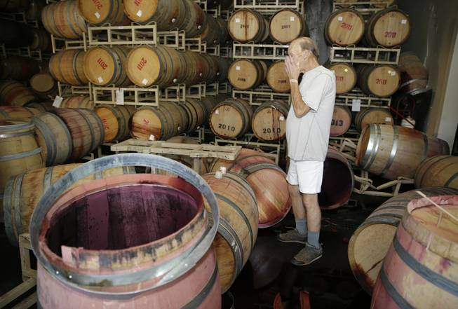 Winemaker Tom Montgomery stands in wine and reacts to seeing damage following an earthquake at the B.R. Cohn Winery barrel storage facility Sunday, Aug. 24, 2014, in Napa, Calif. Winemakers in California's storied Napa Valley woke up to thousands of broken bottles, barrels and gallons of ruined wine as a result of Sunday's earthquake. (AP Photo/