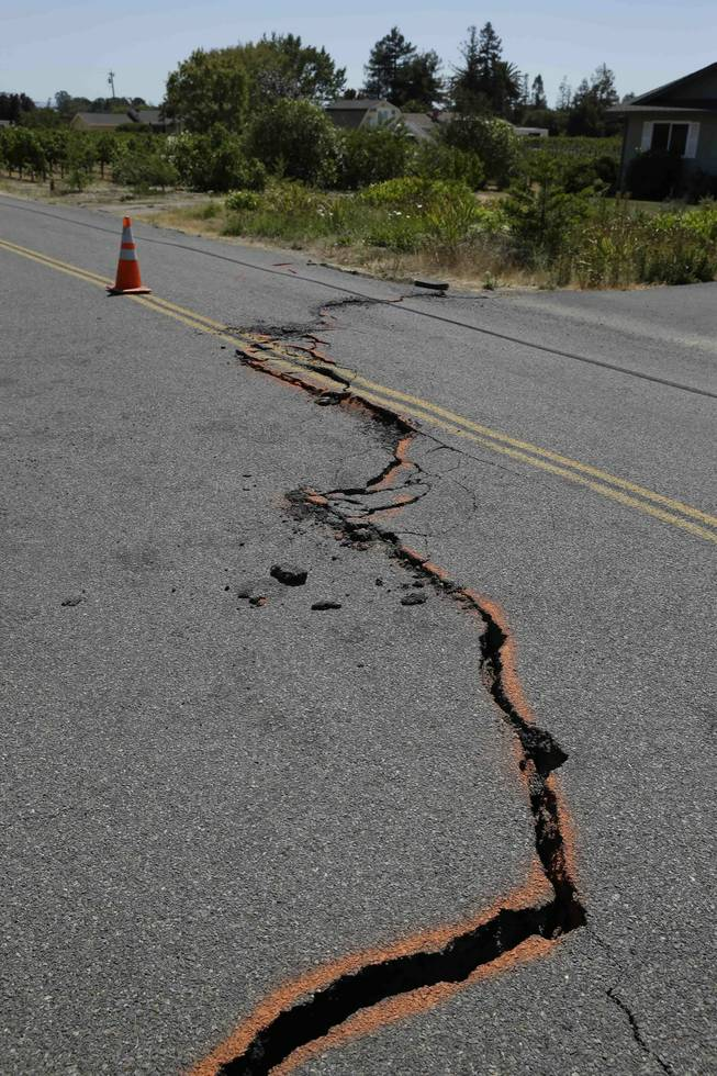 A cracked section of roadway is shown in the Carneros district following an earthquake Sunday, Aug. 24, 2014, in Napa, Calif. The largest earthquake to hit the San Francisco Bay Area in 25 years struck before dawn on Sunday, sending scores of people to hospitals, igniting fires, damaging historic buildings and knocking out power to thousands of homes and businesses in California's wine country.