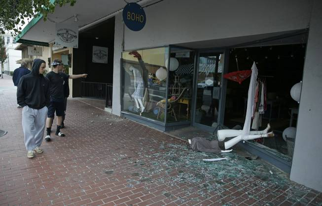 People walk past a tumbled mannequin and broken storefront window on First Street following an earthquake Sunday, Aug. 24, 2014, in Napa, Calif. A large earthquake rolled through California's northern Bay Area early Sunday, damaging some buildings, igniting fires, knocking out power to tens of thousands and sending residents running out of their homes in the darkness.