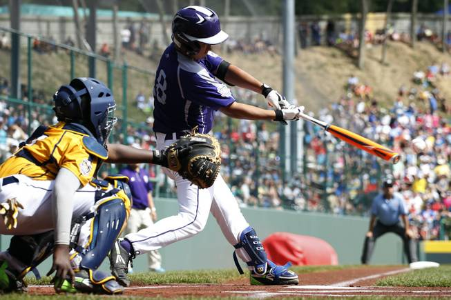South Korea's Jae Yeong Hwang hits an RBI-double off Chicago's Brandon Green during the first inning of the championship baseball game at the Little League World Series, Sunday, Aug. 24, 2014, in South Williamsport, Pa. Chicago catcher Joshua Houston, left, looks on. South Korea won 8-4.