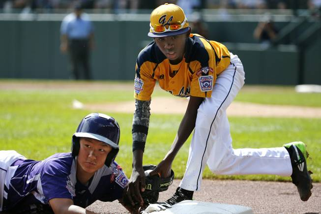 South Korea's Jae Yeong Hwang, left, is tagged out by Chicago's Cameron Bufford while attempting to steal third in the first inning of the Little League World Series championship baseball game in South Williamsport, Pa., Sunday, Aug. 24, 2014.