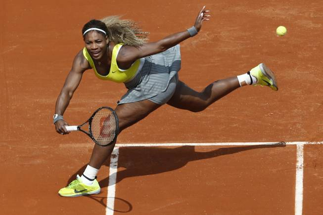 Serena Williams returns the ball during a first round match of the French Open tennis tournament against France's Alize Lim at the Roland Garros stadium, in Paris, France. Serena Williams could become the first woman in nearly 40 years to win three consecutive U.S. Opens, but she has not been past the fourth round at a major in 2014.