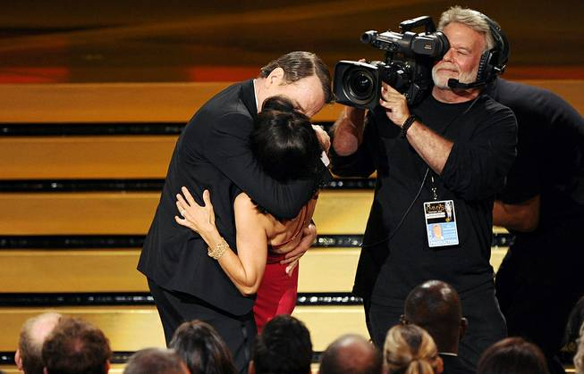 "Bryan Cranston kisses Julia Louis-Dreyfus as she accepts the award for outstanding lead actress in a comedy series for her work on ""Veep"" at the 66th Annual Primetime Emmy Awards at Nokia Theatre L.A. Live on Monday, Aug. 25, 2014, in Los Angeles."