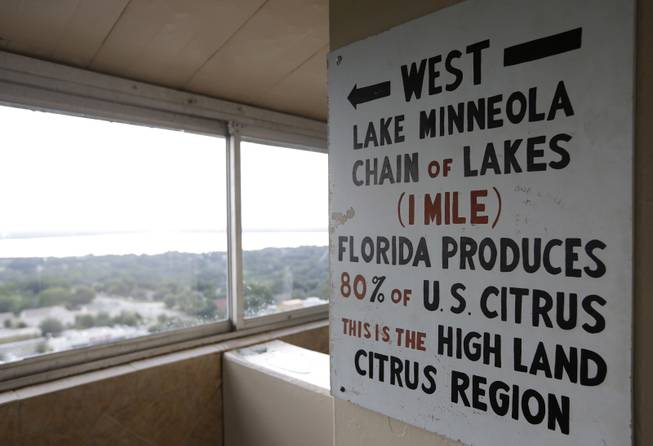 In this Friday, July 25, 2014 photo, a sign in the Florida Citrus Tower points west to Florida's citrus growing region, in Clermont, Fla. The observation tower was built in 1956 as a tourist attraction to view miles of citrus groves. Today Florida's $9 billion citrus industry is facing its biggest threat yet by a tiny invasive bug called the Asian Citrus Psyllid, which carries bacteria that are left behind when the psyllid feeds on a citrus tree's leaves. Eventually disease clogs the tree's vascular system and the tree slowly dies.