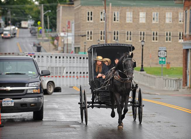 "In this Aug. 15, 2014, file photo, an Amish family rides along Route 812 in Heuvelton, N.Y., near the command center of the investigation into the abduction and return of two young Amish girls at the Heuvelton Volunteer Fire Department. Members of an extended Amish family plan to hold a ""garage raising"" for the couple who returned the two kidnapped Amish girls to their home, according to the the Watertown Daily Times."
