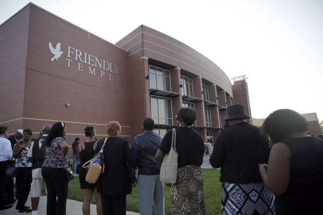 People begin to line up for the funeral of Michael Brown, Monday, Aug. 25, 2014, in St. Louis. Brown, who is black, was unarmed when he was shot Aug. 9, by Officer Darren Wilson, who is white. A grand jury is considering evidence in the case and a federal investigation is also underway.