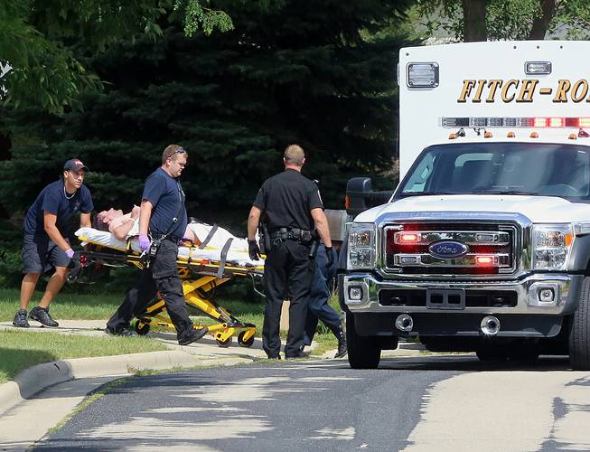 In this Aug. 22, 2014 photo emergency personnel transport Andy Steele, a recently retired Dane County sheriff's deputy, from his hom in Fitchburg, Wis. Authorities said Steele, 39, has been arrested in the fatal shooting of his wife, Ashlee Steele, 39, and sister-in-law, Kacee Tollesfsbol, 38, who were found shot dead in the Steele home.