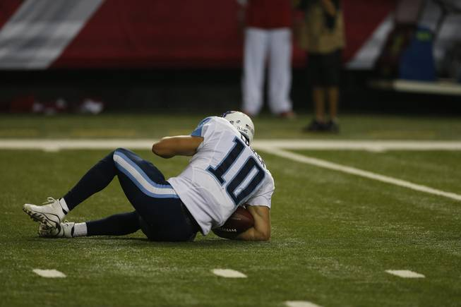 Tennessee Titans quarterback Jake Locker (10) lies on the field after a sack against the Atlanta Falcons during the first half of an NFL preseason football game, Saturday, Aug. 23, 2014, in Atlanta.