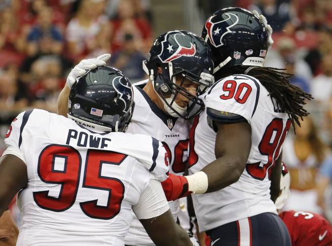 Houston Texans defensive end J.J. Watt, center, celebrates his sack with teammates Jadeveon Clowney (90) and Jerrell Powe (95) during the first half of an NFL preseason football game against the Arizona Cardinals, Saturday, Aug. 9, 2014, in Glendale, Ariz.