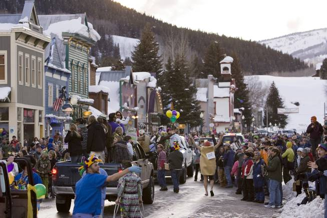 In this Feb. 24, 2009, file photo, a crowd gathers on Elk Avenue in Crested Butte, Colo., during a Mardi Gras parade celebration.