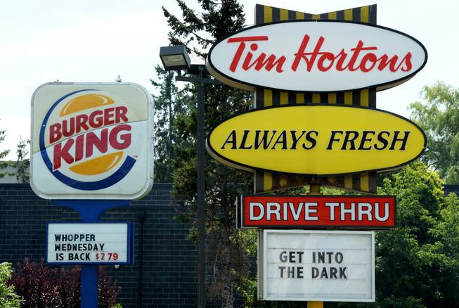 A Burger King sign and a Tim Hortons sign are displayed on St. Laurent Boulevard in Ottawa, Canada, on Monday, Aug. 25, 2014.
