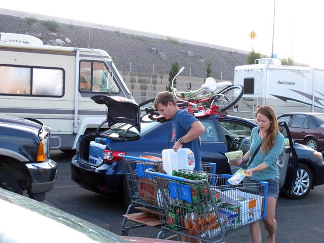 Jeff Difabrizio, left, and Jahliele Paquin of Yellowknife, Canada, load up provisions in the parking lot of a Wal-Mart, Monday, Aug. 25, 2014, in Reno on their first trek to Burning Man. More than 100 recreational vehicles camped out at the Wal-Mart and a Reno casino Monday night when a rare rain storm turned the Black Rock Desert, 90 miles north, into a muddy quagmire.