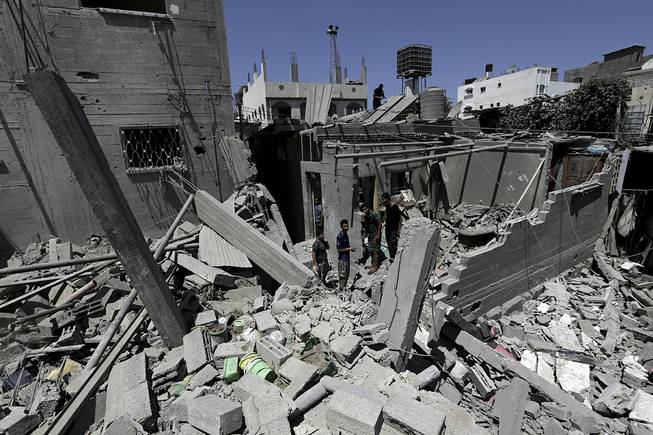 Palestinians, who are neighbors of a house belonging to Abu Hamada family, inspect the damage to their houses, after an Israeli strike in Jebaliya refugee camp, in the northern Gaza Strip, Monday, Aug. 25, 2014. Fifteen people were wounded in an airstrike on houses in Jebaliya refugee camp, according toGaza health official Ashraf al-Kidra.
