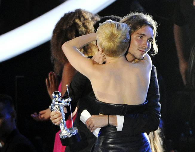 In this Sunday, Aug. 24, 2014 photo, Miley Cyrus hugs Jesse Helt at the MTV Video Music Awards at the Forum in Inglewood, Calif. The young homeless man who accompanied Cyrus to the VMAs has a warrant out for his arrest in Oregon. Helt gained worldwide attention Sunday when Cyrus let him accept her award for Video of the Year.