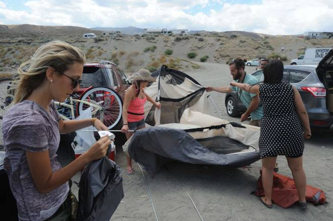 Tania Shoemaker reads the directions to her friends as they attempt to raise the second room of a two-room tent Monday at Pyramid Lake. Like hundreds of other Burners turned away at the playa due to storms, Shoemaker's group ended up at Pyramid Lake.