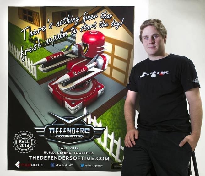 "John Flury is CEO of Four Lights, a self-producing and self-publishing video game company on Wednesday, August 27, 2014. He is with a poster about their first release which is a multiplayer tower defense game ""Defenders of Time,"" slated for official release in September. L.E. Baskow"