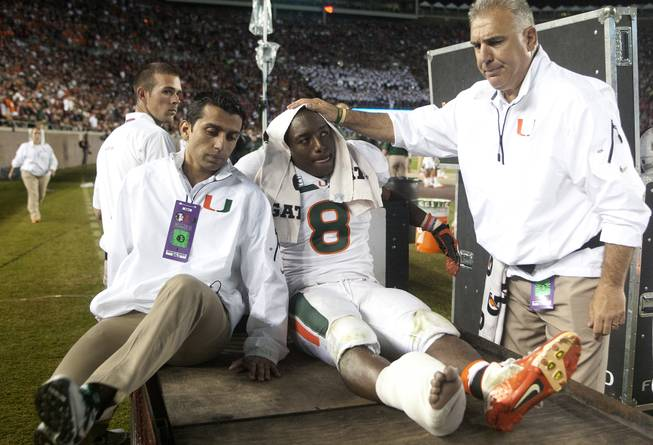 Miami running back Duke Johnson is consoled as he is taken off the field after injuring his foot during the third quarter of an NCAA college football game against Florida State on Saturday, Nov. 2, 2013, in Tallahassee, Fla.