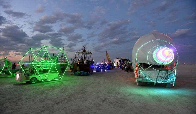 In this Sunday night, Aug. 23, 2014 photo, art cars are lined up to be registered at the Black Rock DMV during the annual Burning Man event on the Black Rock Desert of Gerlach, Nev.