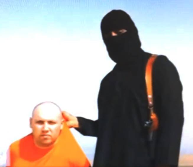 This still image from an undated video released by Islamic State militants on Tuesday, Aug. 19, 2014, purports to show journalist Steven Sotloff being held by the militant group.