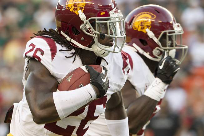 In this Aug. 29, 2013, file photo, Southern California cornerback Josh Shaw (26) runs back an interception for a touchdown against Hawaii during the second quarter of an NCAA college football game in Honolulu. The university is investigating his story that he injured both of his ankles jumping off a balcony to save his nephew from drowning.