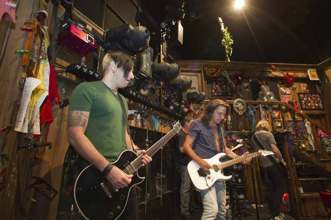 "Guitarist Andy Gerold, left, guitarist Chris Cicchino, center, and bassist Dan Grennes test out equipment before a performance of ""Rock Of Ages"" at the Venetian Wednesday, Aug. 27, 2014."