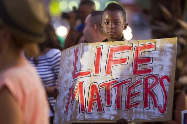 Derric Marshall, 7, holds a sign during a vigil for Michael Brown at Martin Luther King Boulevard and Carey Avenue Thursday, August 28, 2014. Brown, 18, was shot and killed by a police officer Aug. 9, 2014 in Ferguson, Mo.